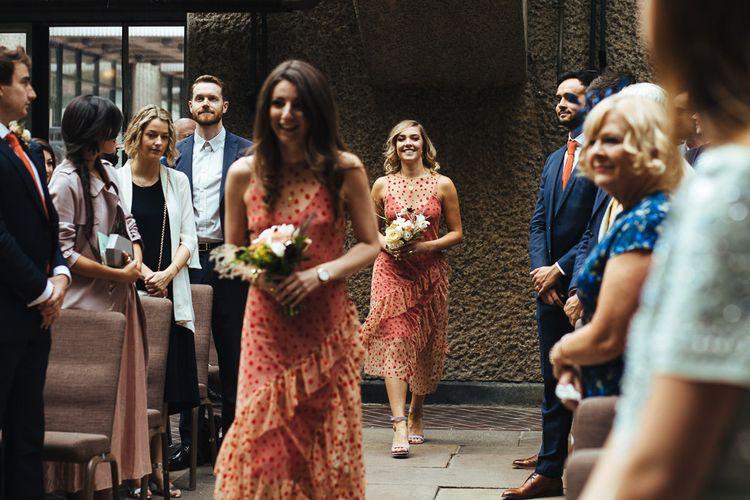 Bridesmaids in Sheer Orange Polka Dot Dresses Walking Down the Aisle