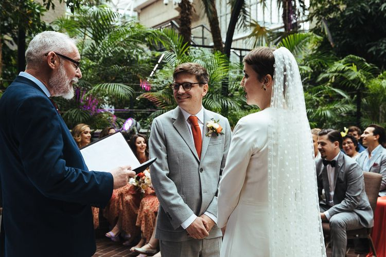 Groom in Grey Suit and Orange Tie and Bride in Cathedral Length Polka Dot Veil Standing at the Altar