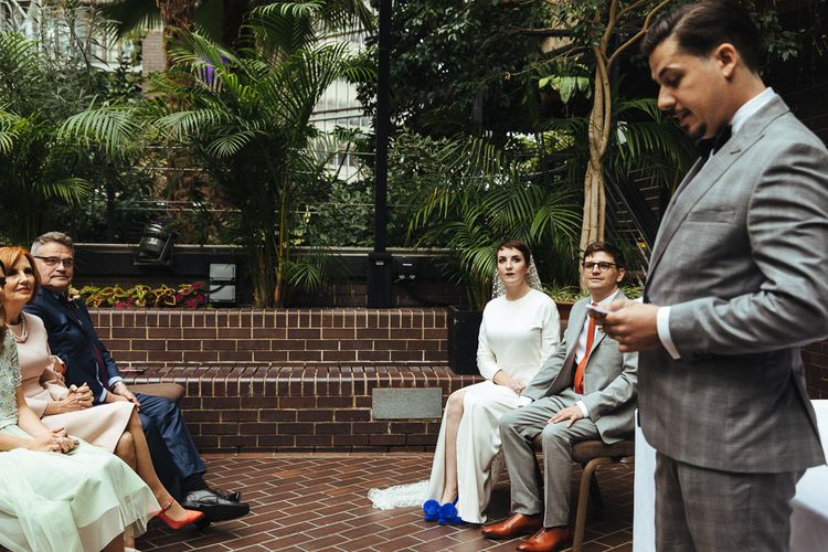 Bride in Cobalt Blue Shoes with Pom Poms and Groom in Grey Suit Sitting During a Wedding Ceremony Reading