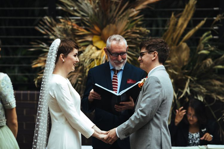 Bride in Minimalist Charlie Brear Wedding Dress with Long Sleeves and Groom in Grey Suit Holding Hands During the Wedding Ceremony