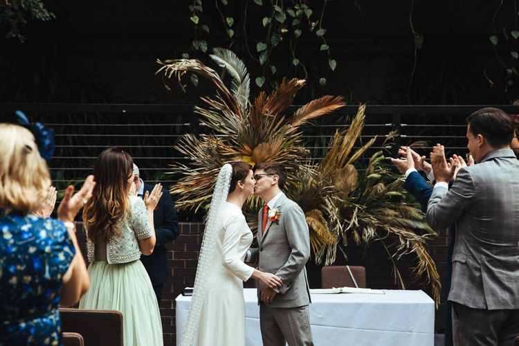 Bride and Groom Kissing at the Altar with Dried Fern Backdrop Flowers