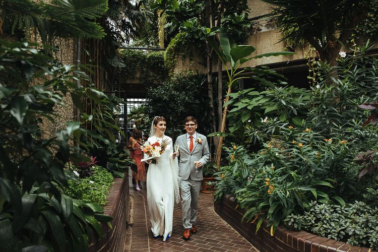Bride in Charlie Brear Wedding Dress and Groom in Light Grey Suit Walking Around Barbican Conservatory in London
