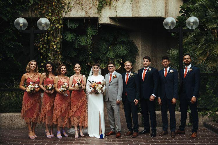Wedding Party Portrait with Bridesmaids in Polka Dot Sheer Zara Dresses, Bride in Charlie Brear Dress with Long Sleeves, Groom in Light Grey Suit and Groomsmen in Navy Suits with Orange Ties