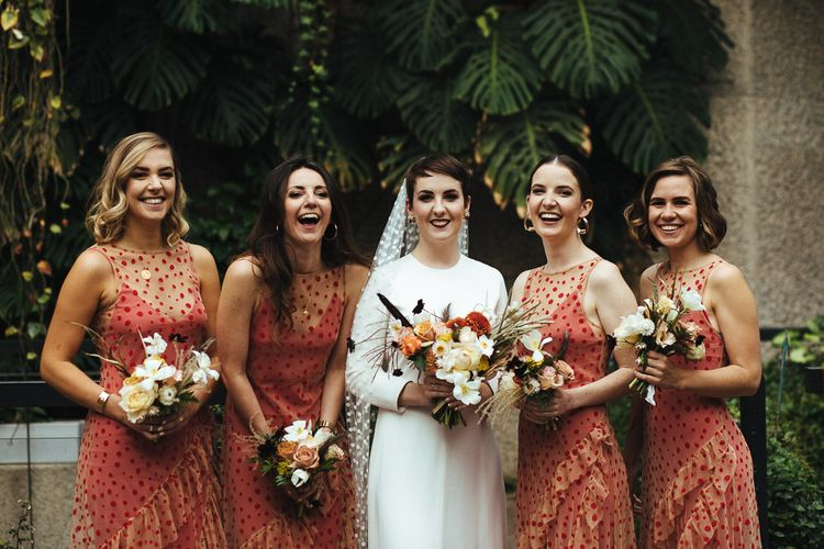 Bridal Party Portrait with Bridesmaids in Sheer Orange Polka Dot Dresses and Bride in Minimalist Charlie Brear Wedding Dress with Long Sleeves and Polka Dot Wedding Veil