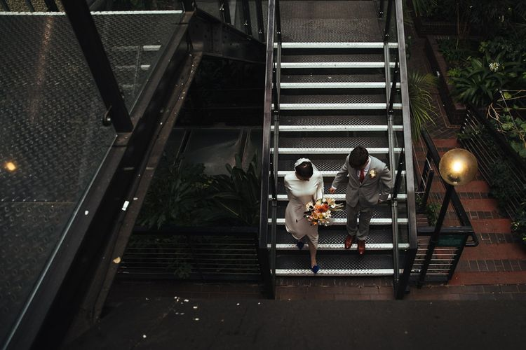 Bride in Charlie Brear Minimalist Wedding Dress and Groom in Grey Suit Walking Down the Stairs Together
