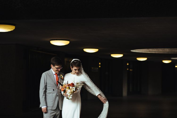Bride in Charlie Brear Wedding Dress and Polka Dot Veil and Groom in Light Grey Suit