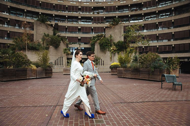 Bride in Charlie Brear Wedding Dress and Electric Blue Pom Pom Shoes and Groom in Light Grey Suit