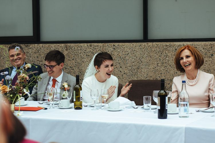 Bride with Pixie Hair Cut Laughing During Wedding Reception Speeches