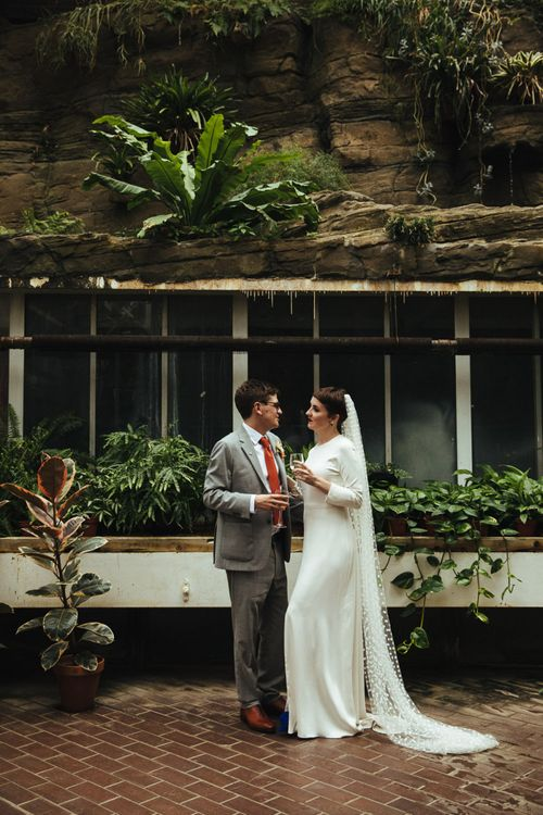 Bride in Charlie Brear Wedding Dress and Polka Dot Wedding Veil and Groom in Light Grey Suit Enjoying a Glass of Champagne Together