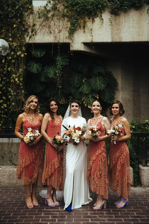 Bridal Party Portrait with Bridesmaids in Sheer Polka Dot Orange Dresses and Bride in Minimalist Charlie Brear Wedding Dress