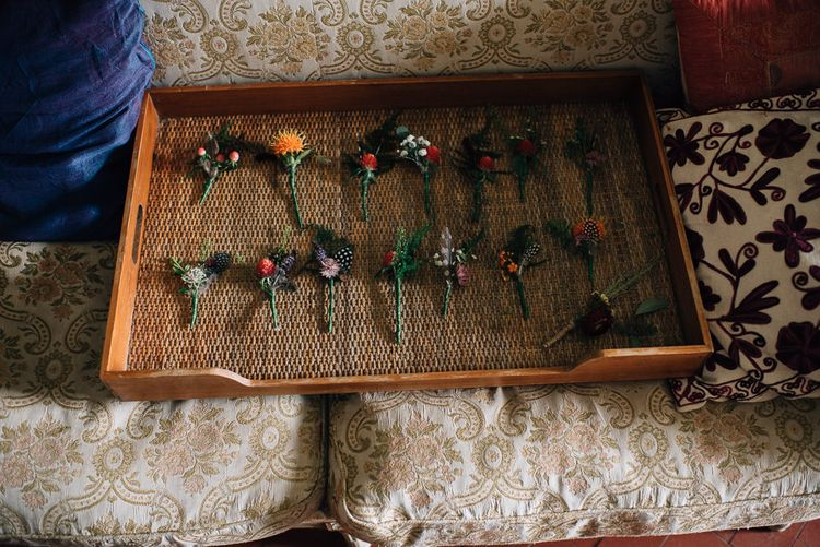Tray of Unique Buttonholes with Feathers and Flower Stems