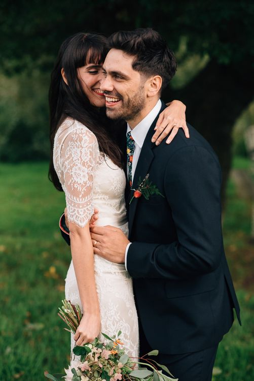 Bride in Catherine Deane Wedding Dress with Wild Flower Bouquet and Groom in Paul Smith Suit and Floral Liberty Print Tie Embracing
