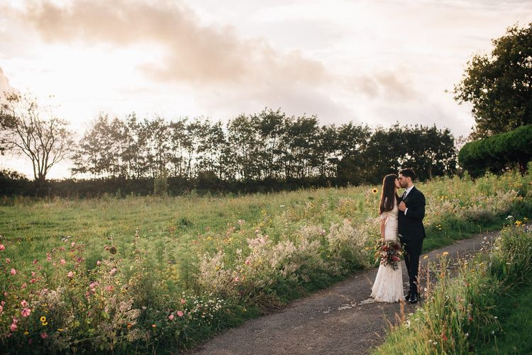 Bride in Catherine Deane Wedding Dress with Wild Flower Bouquet and Groom in Paul Smith Suit and Floral Liberty Print Tie Standing in Country Lane