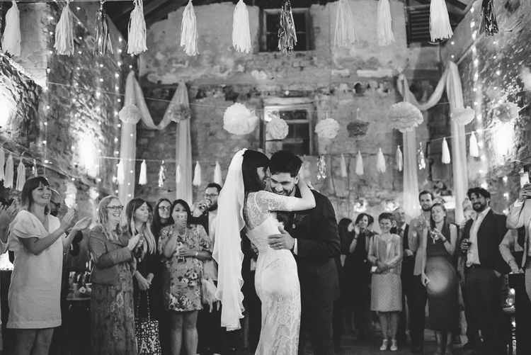 Bride and Groom Enjoying First Dance with Tissue Tassels and Pom Pom Ceiling Decor