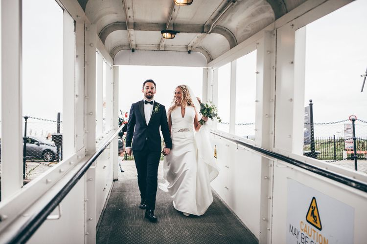 Bride in Satin Jesus Peiro Dress with V-Neck and Waist Bow with Beaded Belt | Floor Length Double Tier Veil with Blusher | Bridal Bouquet of White Flowers and Foliage | Groom in Black Tie Suit from Moss Bros. with Bow Tie | Nautical Wedding on SS Nomadic Boat in Belfast with Black Tie Dress Code | Sarah Gray Photography