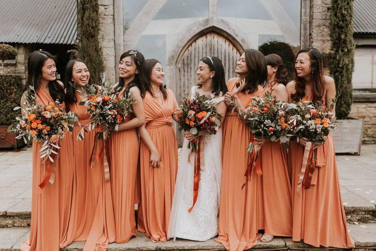 Bridal party portrait with bridesmaids in orange dresses for Autumn dresses