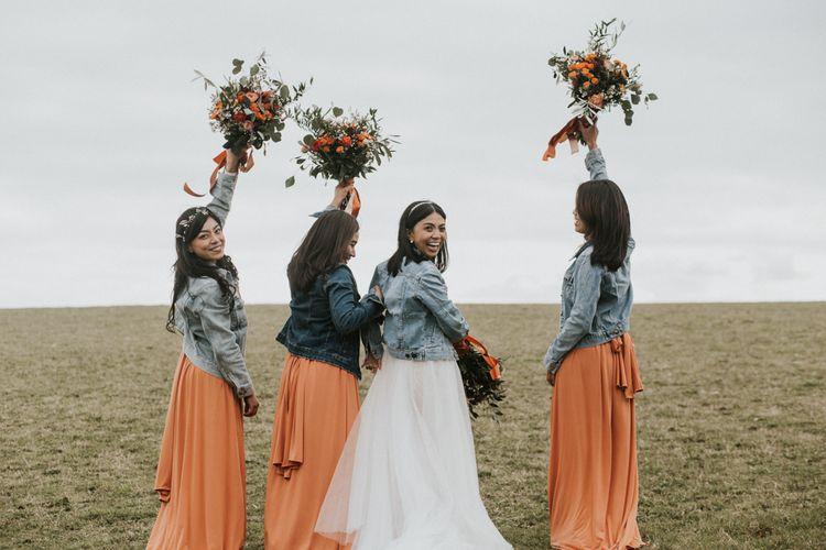 Bride and bridesmaids portrait in a field at Cripps Barn wedding venue