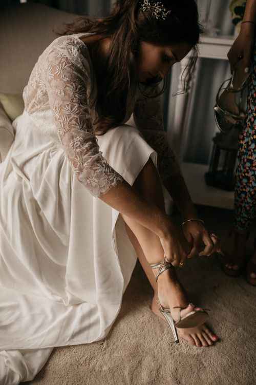 Bride in Donatelle Godart Wedding Dress Putting on Chloé Bridal Shoes