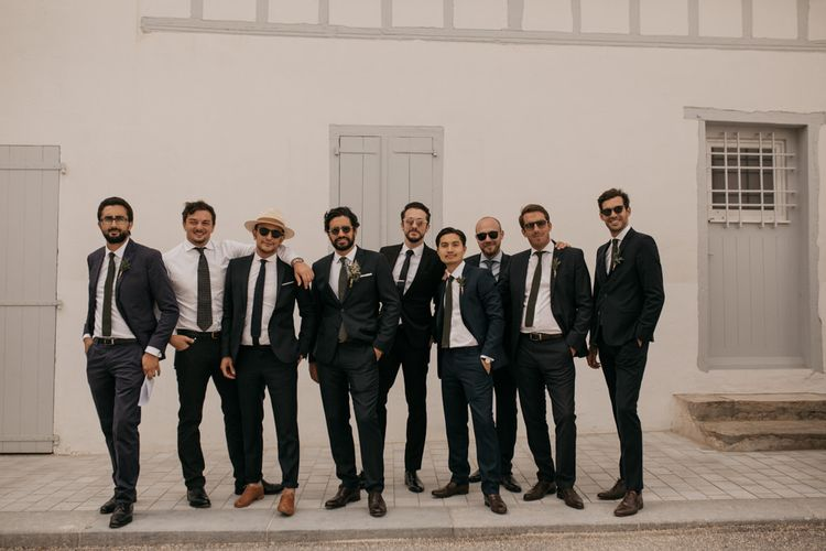 Stylish Groom in Black De Fursac Suit with Groomsmen
