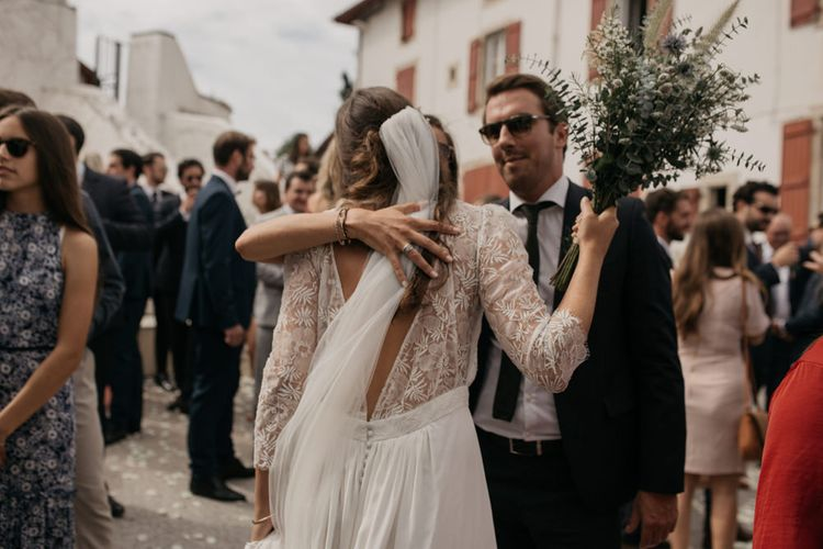 Bride in Donatelle Godart Wedding Dress with Lace V Back and Long Sleeves Hugging Guests