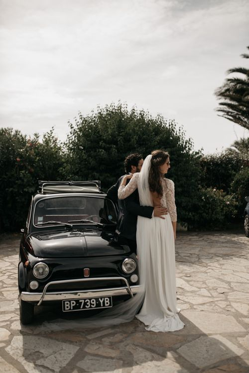 Bride in Donatelle Godart Wedding Dress & Groom in De Fursac Suit Standing Next to a Fiat 500 Wedding Car