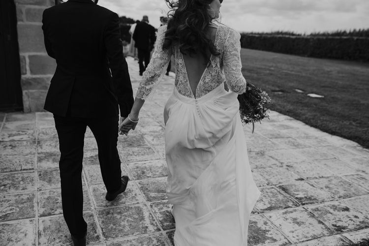 Bride in Donatelle Godart Wedding Dress with Lace V Back & Groom in De Fursac Suit Holding Hands