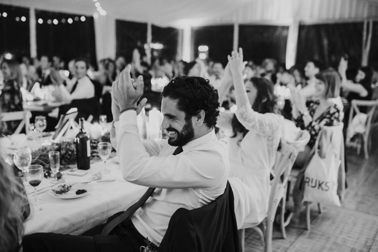 Groom in De Fursac Suit Clapping During Evening Reception