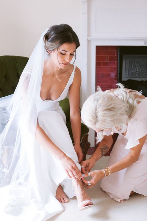 Bride in simple dress puts on nude wedding shoes