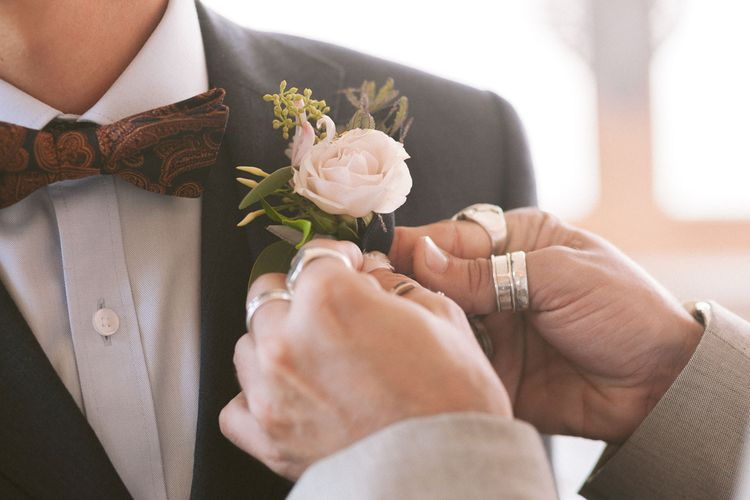 Blush rose buttonhole for groom in bowtie