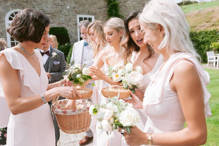 Bridesmaids in blush dresses take confetti from basket