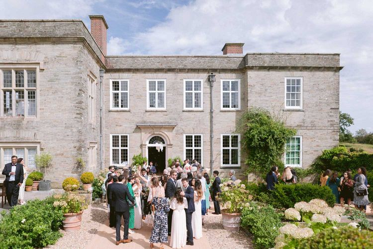 Guests enjoy a drink out Shilstone House wedding venue in Devon