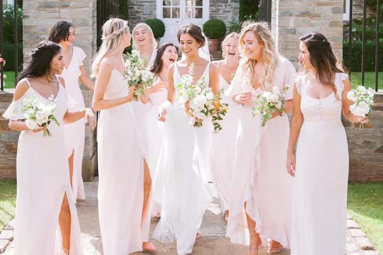 Bridesmaids in pink dresses with bride in simple wedding dress