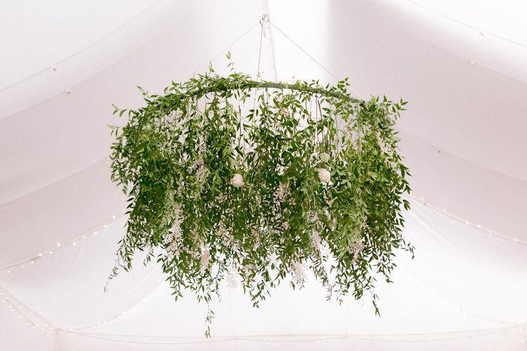 Foliage chandelier hanging above dinner reception