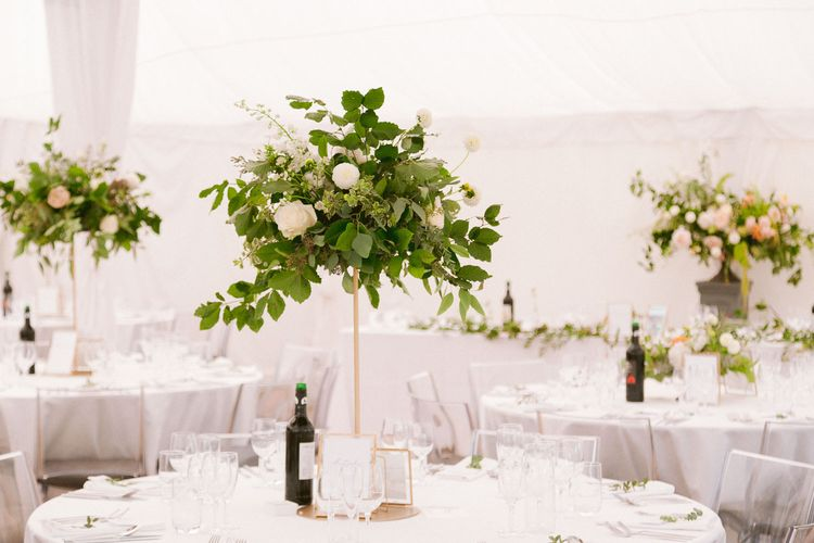 Tall wedding table centrepieces with gold detail and flowers and foliage