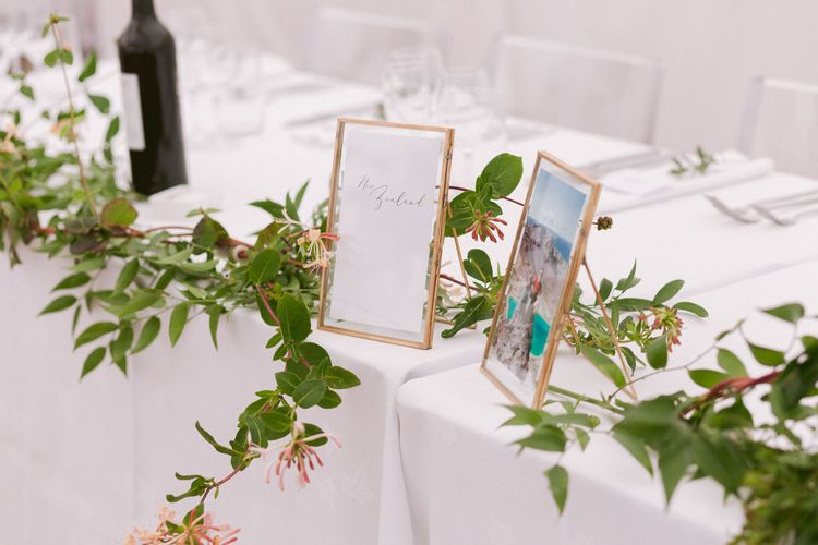 Wedding table decor with foliage and photo frames