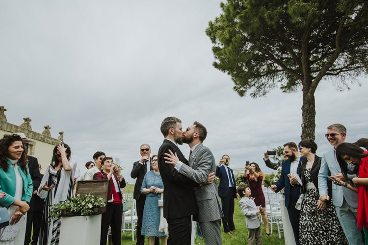 Grooms kiss after wedding ceremony