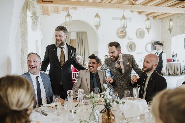Grooms speak to guests during wedding breakfast in grey groom suit
