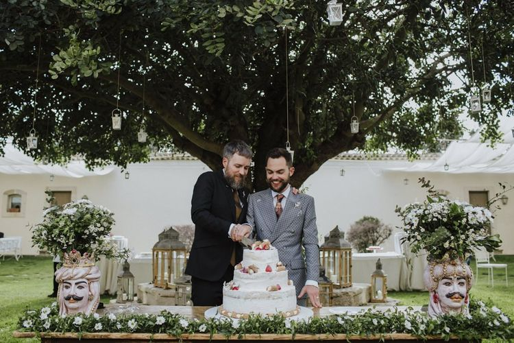 Groom and groom cut the wedding cake in grey groom suit