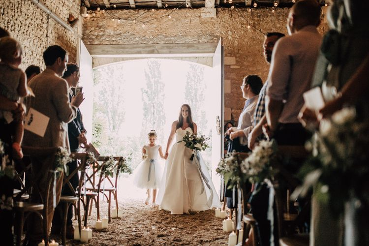 Wedding ceremony bridal entrance with bride in strapless dress  and flower girl in a tutu