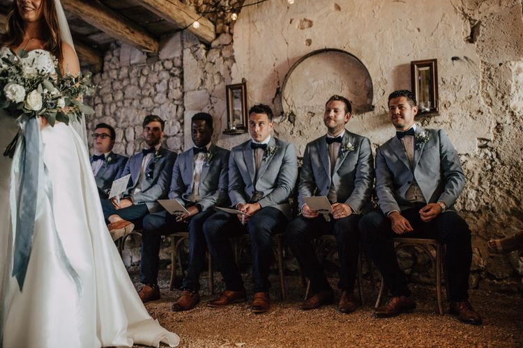 Groomsmen in navy chinos and blue blazers at the wedding ceremony