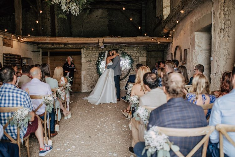Bride in Sassi Holford wedding dress kissing her groom at the neon light altar