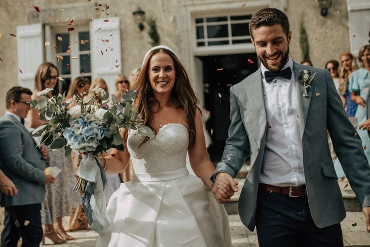 Confetti Exit with bride in strapless Sassi Holford wedding dress and groom in blue blazer and bow tie