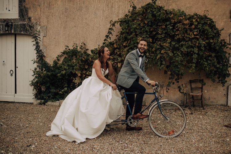 Bride in princess wedding dress and groom in blue blazer riding a tandem bicycle