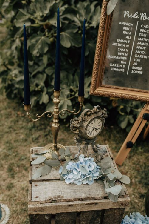 Candlestick and clock wedding decor on a rustic crate