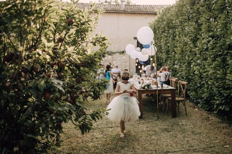 Flower girl in white leotard and tutu with blue bows