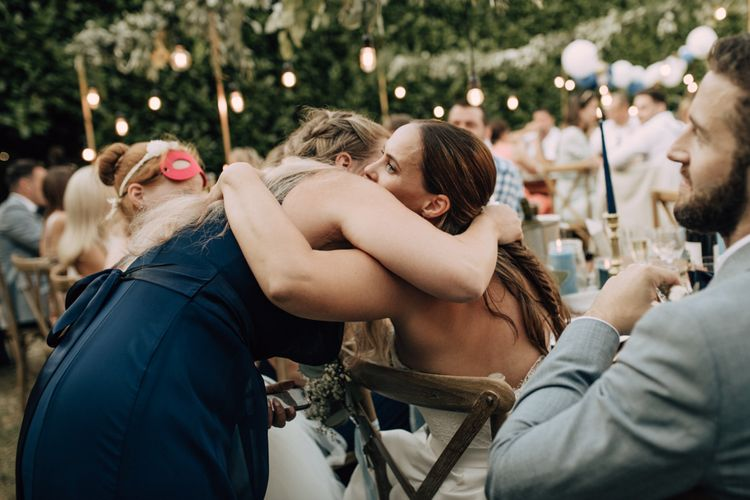 Wedding guests embracing the bride during wedding reception speeches