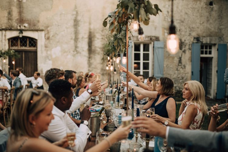 Outdoor wedding reception with wedding lighting above the tables