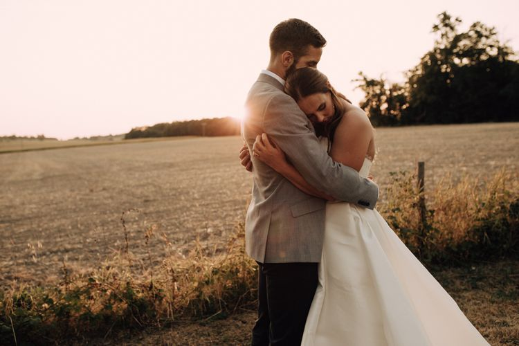 Golden hour portrait with groom embracing his bride in a Sassi Holford wedding dress
