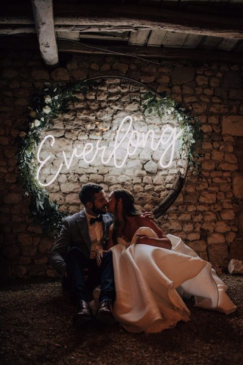 Bride and groom kissing in front of a hoop neon wedding sign.