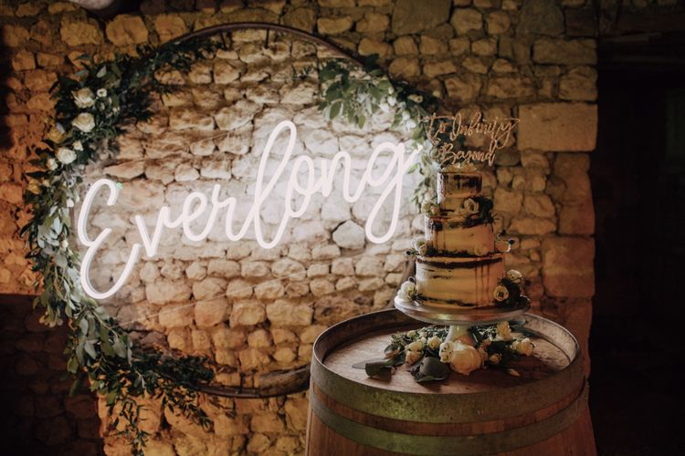 Semi naked wedding cake on a barrel in front of a white neon everything sign